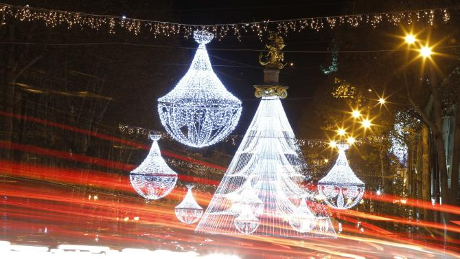 Cars drive on a street illuminated with Christmas lights in Tbilisi