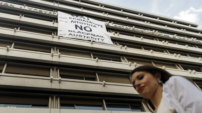A woman passes a banner supporting the NO vote to the upcoming referendum at the Finance Ministry in Athens, Wednesday, July 1, 2015. Greece's government appeared to be caving into demands from its creditors on Wednesday, offering concessions in a desperate attempt to get more aid hours after its bailout program expired. (AP Photo/Daniel Ochoa de Olza)
