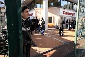 A police officer stands guard at the entrance of Cumhuriyet, …