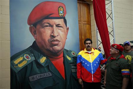 Venezuelan Vice President Nicolas Maduro and National Assembly President Diosdado Cabello stand next to a painting of Venezuelan President Hugo Chavez as they attend the commemoration of the 21st anniversary of Chavez's attempted cuop d'etat in Caracas