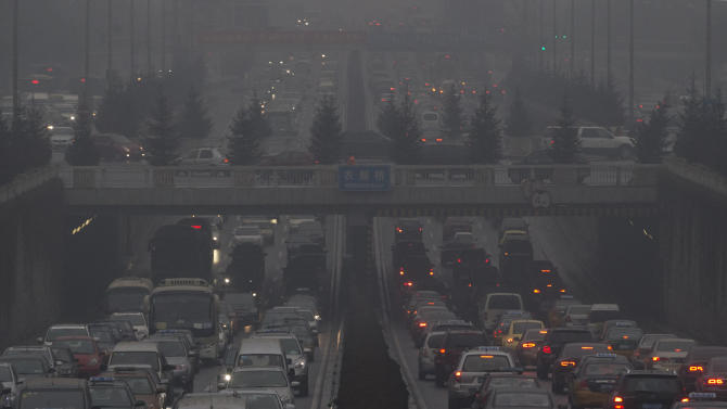 Vehicles crawl along a major road in Beijing, China, Thursday, Jan. 31, 2013. Endless lines of slow-moving cars emerge like apparitions and disappear into the gloom of the thick smog that has shrouded Beijing for weeks and reduced its skyline to blurry gray shapes. With more than 12 million cars sold in China last year, motor vehicles have emerged as the chief culprit for the throat-choking air pollution in big cities especially Beijing.(AP Photo/Ng Han Guan)