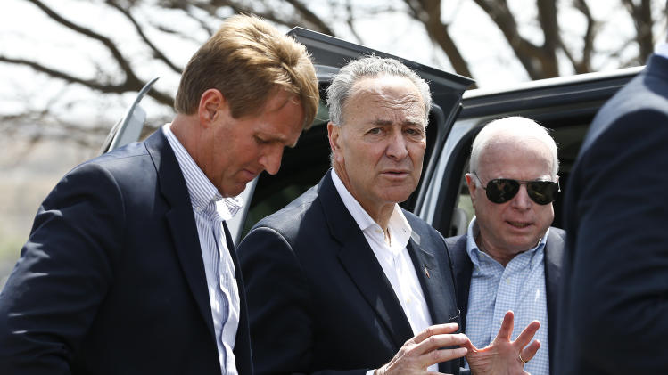 Sen. John McCain, R-Ariz., right, and Sen. Jeff Flake, R-Ariz., left, listen as Sen. Chuck Schumer, D-N.Y., talks prior to a news conference after their tour of the Mexico border with the United States on Wednesday, March 27, 2013, in Nogales, Ariz   The senators are part of a larger group of legislators, including Sen. Michael Bennett, D-CO, who also joined the three at the border for the tour, who are shaping and negotiating details of an immigration reform package vowed Wednesday to make the legislation public when Congress reconvenes next month. (AP Photo/Ross D. Franklin)
