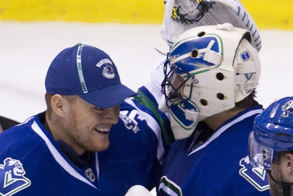 Vancouver Canucks goalie Roberto Luongo (1) celebrates his teams win with fellow goalie and teammate Cory Schneider (35) after an NHL hockey game against the Edmonton Oilers at Rogers Arena in Vancouver, British Columbia, Saturday, April, 7, 2012. (AP Photo/The Canadian Press, Jonathan Hayward)