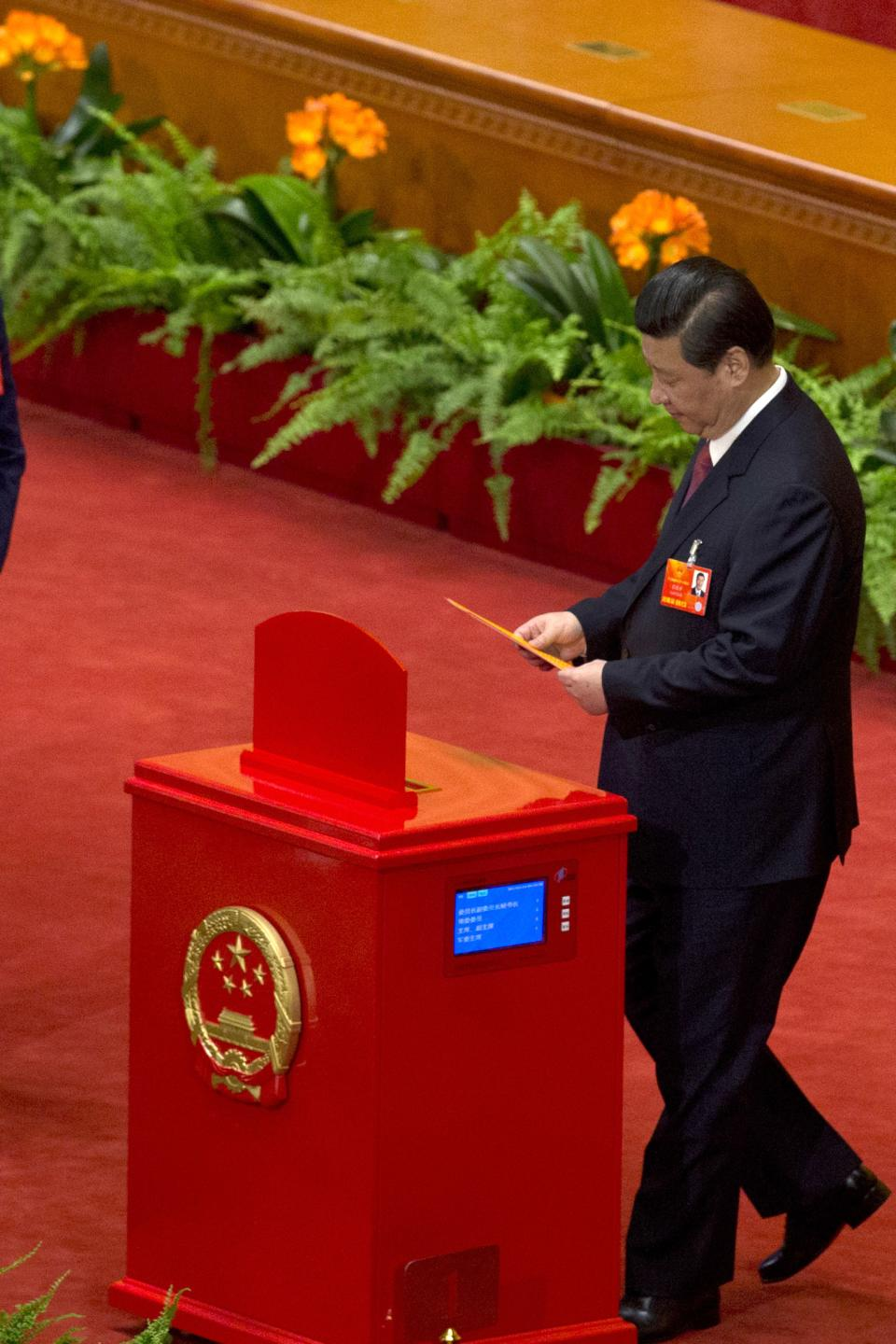 Chinese Communist Party chief and incoming-President Xi Jinping prepares to cast his votes at a plenary session of the National People's Congress where delegates are expected to elect Xi officially as president at the Great Hall of the People in Beijing Thursday, March 14, 2013. (AP Photo/Ng Han Guan)