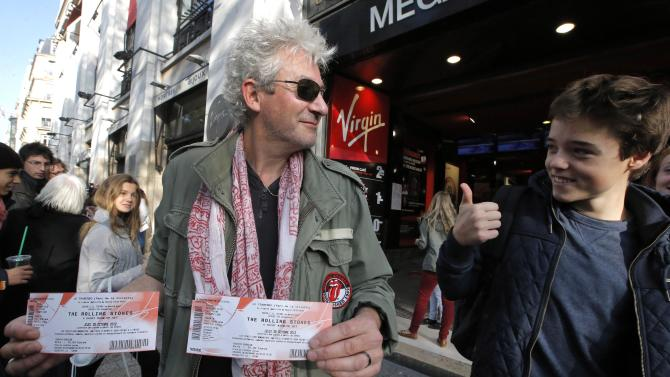 "Rolling Stones fan who named himself Patrice, 55, left, and who claims he has seen 54 Rolling Stones concerts, shows the tickets he bought for Thursday night's concert in Paris, Thursday, Oct. 25, 2012. The Rolling Stones announced a surprise ""warm-up gig"" in Paris, and within an hour the Champs Elysees was swarming with fans hoping to get satisfaction with one of the 350 tickets for the Thursday night show. (AP Photo/Francois Mori)"