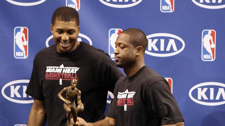 "Miami Heat guard Dwyane Wade, right, jokingly grabs LeBron James' NBA MVP trophy as he and teammate Dexter Pittman leave the stage after a ceremony to present the award to James, Saturday, May 12, 2012 in Miami. Calling the honor ""overwhelming"" but pointing to a ""bigger goal,"" James on Saturday became the eighth player in NBA history to win the MVP award three times. (AP Photo/Wilfredo Lee)"