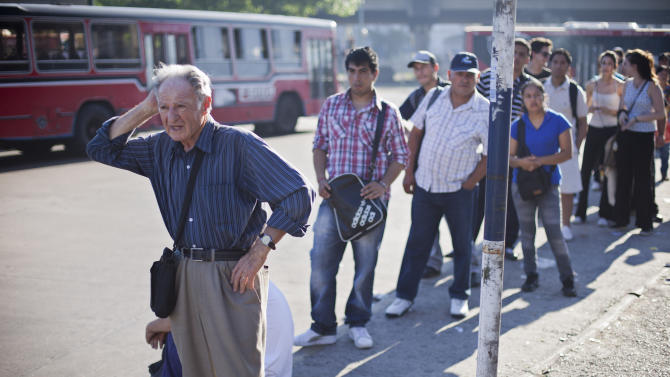 People wait in line for a bus during a general strike in Buenos Aires, Argentina,  Tuesday, Nov. 20, 2012.  Argentina's biggest unions are holding their first national strike against President Cristina Fernandez to demand a higher minimum wage and protest against rising inflation,  among other demands.(AP Photo/Victor R. Caivano)