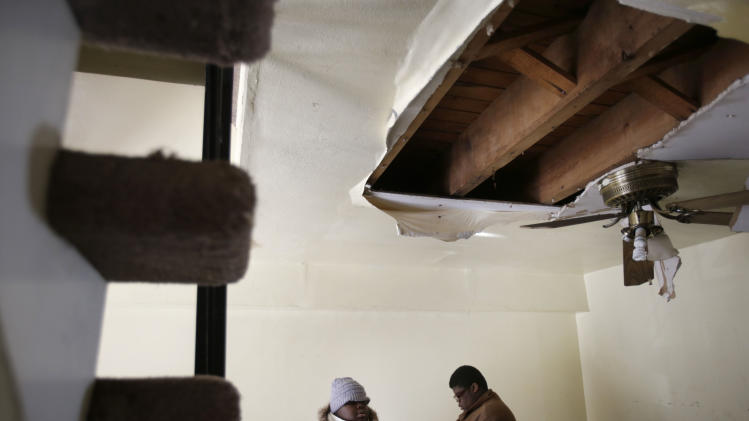 Ayanna Diego and her son William Diego stand in their dining room, which was damaged during Superstorm Sandy, at their home in the Rockaways section of New York, Thursday, Jan. 24, 2013. Not only was the basement flooded, but water leaked through the roof and damaged the higher floors as well. (AP Photo/Seth Wenig)