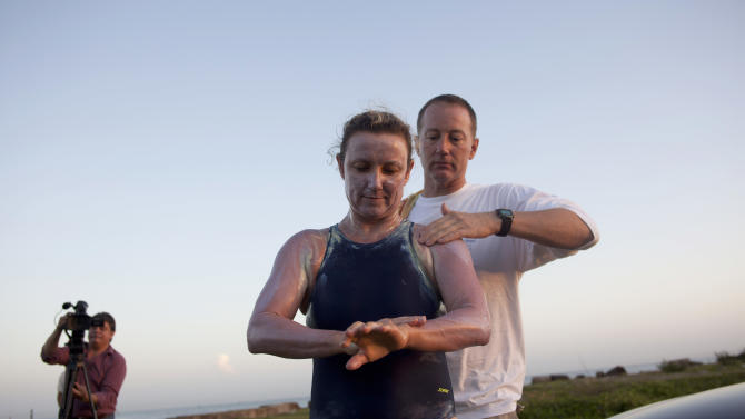 British-Australian swimmer Penny Palfrey and her husband Chris rub creme on her body in preparation for her bid to complete a record swim from Cuba to Florida, in Havana, Cuba, Friday, June 29, 2012. Palfrey aims to be the first woman to swim the Straits of Florida without the aid of a shark cage. Instead she's relying on equipment that surrounds her with an electrical field to deter the predators. (AP Photo/Ramon Espinosa)