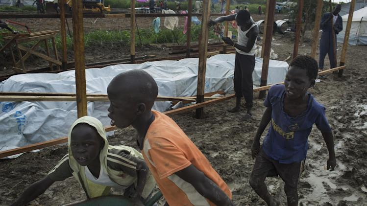 "In this photo of Thursday, July 24, 2014, children moving a bag of grain through the mud with a wheel burrow from a food distribution through the new United Nations' Malakal Camp for Internally Displaced People, (IDP) during the wet season which has made life for hundreds of thousands of IDPs in South Sudan very challenging, in Malakal, Sudan. Health experts are meeting in South Sudan's capital, Juba, Monday July 28, 2014, debating exactly how severe the famine situation is in South Sudan, and their decision may prompt millions of dollars in aid or condemn tens of thousands of displaced people to continued hunger in what is described by Chris Hillbruner, the lead food security analyst for FEWSNET, a famine early warning system ""is still the worst food security emergency in the world ... there is still huge need."" (AP Photo/ Matthew Abbott)"