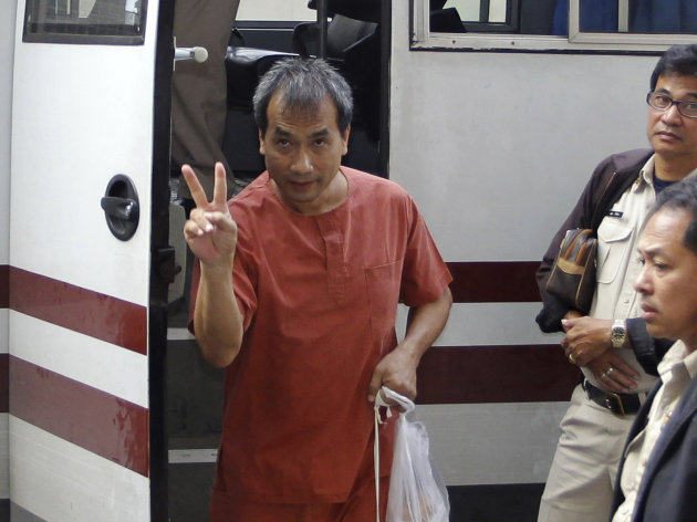 Thai-born American, Joe Gordon, with his ankles shackled, gestures as he arrives at a criminal court in Bangkok, Thailand, Thursday, Dec. 8, 2011. The court in Thailand sentenced Gordon to two and a half years in prison Thursday for defaming the country's royal family by translating excerpts of a locally banned biography of the king and posting them online. (AP Photo/Apichart Weerawong)