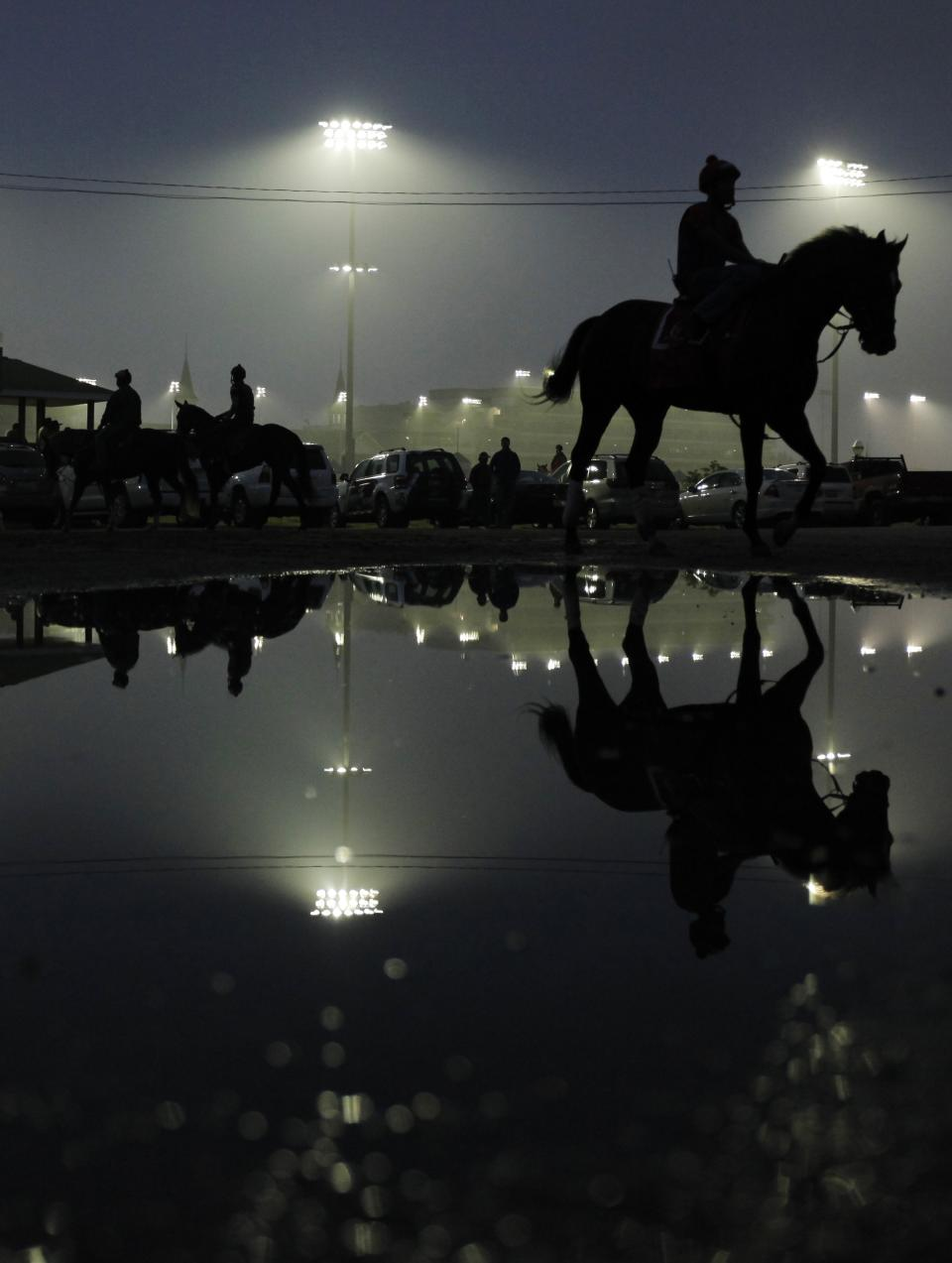 An exercise rider walks a horse off the track at Churchill Downs after a morning workout Tuesday, May 1, 2012, in Louisville, Ky. (AP Photo/Charlie Riedel)