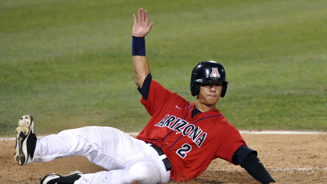 Arizona's Robert Refsnyder scores against South Carolina on a single by Bobby Brown in the seventh inning of Game 1 of the NCAA College World Series baseball finals in Omaha, Neb., Sunday, June 24, 2012. (AP Photo/Dave Weaver)