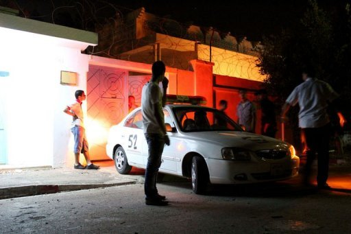 Libyan security forces and onlookers stand outside the Tunisian consulate in the eastern city of Benghazi after gunmen stormed the building
