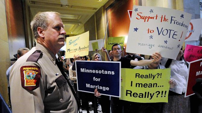 FILE - This May 19, 2011 file photo, a state trooper stands by as demonstrators on both sides of the gay marriage issue gather outside the Minnesota House in St. Paul, Minn. President Obama's Friday, June 1, 2012 visit to Minnesota is his first to a state with a gay marriage ban on its ballot this fall since he declared his support for letting gay couples legally marry. (AP Photo/Jim Mone, File)