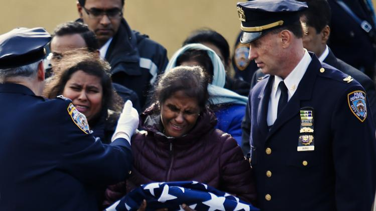 Dammika cries after receiving the flag that covered the casket of her husband during his wake service in New York