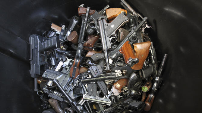 Hand guns that were turned in by their owners are seen in a trash bin at a gun buyback held by the LAPD following the mass shooting at Sandy Hook Elementary School in Connecticut, in Los Angeles