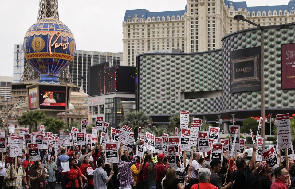 Culinary Union workers demonstrate along Las Vegas Boulevard outside the Cosmopolitan Hotel and Casino while protesting their contract negotiations with Deutsche Bank, Wednesday, March 20, 2013, in Las Vegas. Nearly 98 protestors were arrested during the demonstration. Workers have been in contract talks with Cosmopolitan Las Vegas owner Deutsche  Bank for two years. (AP Photo/Julie Jacobson)