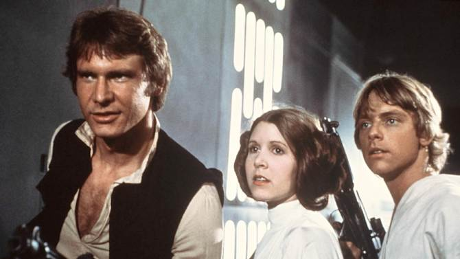"""This publicity film image provided by 20th Century-Fox Film Corporation shows, from left, Harrison Ford as Han Solo, Carrie Fisher as Princess Leia Organa and Mark Hamill as Luke Skywalker in a scene from the """"Star Wars"""" movie released by 20th Century-Fox in 1977. The classic Star Wars film that launched a science fiction empire is being dubbed in the Navajo language, with casting calls scheduled Monday, April 29, 2013, in Burbank, Calif., and on May 3 and 4 at the Navajo Nation Museum in Window Rock.  Potential actors don't have to sound exactly like Princess Leia, Luke Skywalker or Han Solo, but should be able to deliver the lines with character. (AP Photo/20th Century-Fox Film Corporation)"""