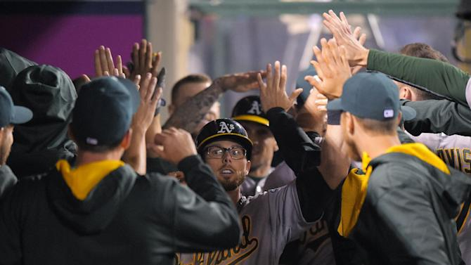 Oakland Athletics' Eric Sogard celebrates with teammates after scoring on a sacrifice fly by Oakland Athletics' Sam Fuld during the ninth inning of a baseball game against the Los Angeles Angels, Monday, April 20, 2015, in Los Angeles. (AP Photo/Mark J. Terrill)