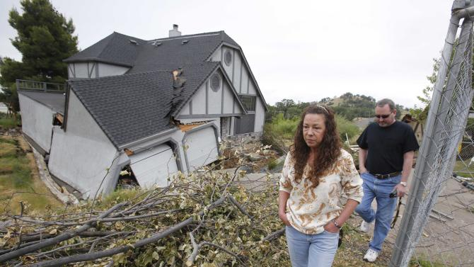 In this photo taken Monday, May 6, 2013  Robin and Scott Spivey walk past the wreckage of their Tudor-style dream home they had to abandon when the ground gave way causing it to drop 10 feet below the street in Lakeport, Calif.  Officials believe that water that has bubbled to the surface is playing a role, in the collapse of the hillside subdivision that has forced the evacuation of 10 homes and the notice of imminent evacuation of another 10 in this upscale subdivision.(AP Photo/Rich Pedroncelli)