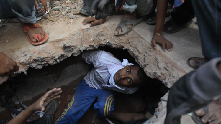 A Bangladeshi rescuer looking for survivors emerges from beneath a concrete slab of a building that collapsed Wednesday in Savar, near Dhaka, Bangladesh,Thursday, April 25, 2013. By Thursday, the death toll reached at least 194 people as rescuers continued to search for injured and missing, after a huge section of an eight-story building that housed several garment factories splintered into a pile of concrete on Wednesday. (AP Photo/A.M.Ahad)