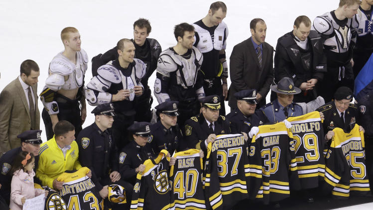 First responders, members of law enforcement and Boston Marathon officials hold Boston Bruins jerseys as they gather with members of the team, back, on the ice following an NHL hockey game against the Florida Panthers at the TD Garden in Boston, Sunday, April 21, 2013. In a change requested by fans, Bruins players presented their jerseys to some of those who offered help in the minutes and days following the marathon bombings on Monday. The Bruins defeated the Panthers 3-0. (AP Photo/Steven Senne)