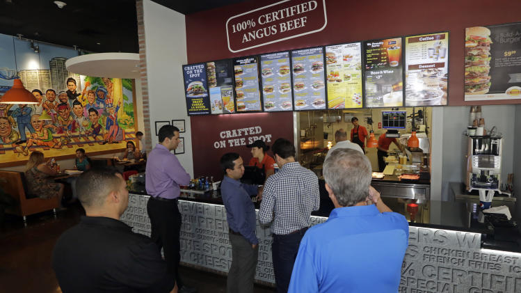 In this photo taken Friday, Aug. 15, 2014, customers line up to order lunch at El Corral restaurant in Miami. Colombian hamburger chain El Corral has over 200 locations in Latin America and arrived to the U.S. in early 2013. (AP Photo/Alan Diaz)