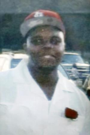 """FILE - This undated photo provided by the Brown family shows Michael Brown. Michael Brown, 18, was shot and killed in a confrontation with police in the St. Louis suburb of Ferguson, Mo., on Saturday, Aug. 9, 2014. Brown suffered a bullet wound to his right arm that may have occurred when he put his hands up or when his back was turned to the shooter, """"but we don't know,"""" a pathologist hired by the teen's family said Monday, Aug. 18, 2014. (AP Photo/Brown Family, File)"""