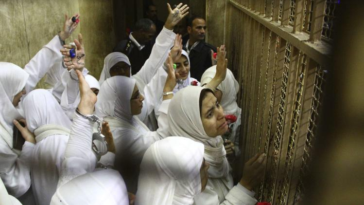 Women, who were found guilty of obstructing traffic during a pro-Islamist protest in October, gesture during their appeal hearing at a court in Alexandria