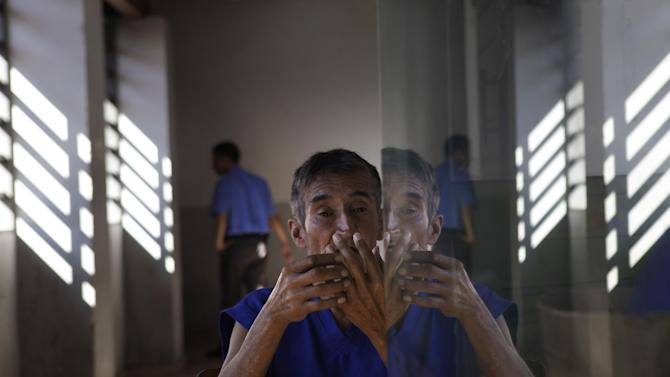 In this May 29, 2013 photo, a patient spends time in the main courtyard of the Neuro-Psychiatric Hospital in Asuncion, Paraguay. Paraguay's only public psychiatric hospital is forced to feed hundreds of patients with donated food for lack of funding. Now, it's running low on medicine. (AP Photo/Jorge Saenz)