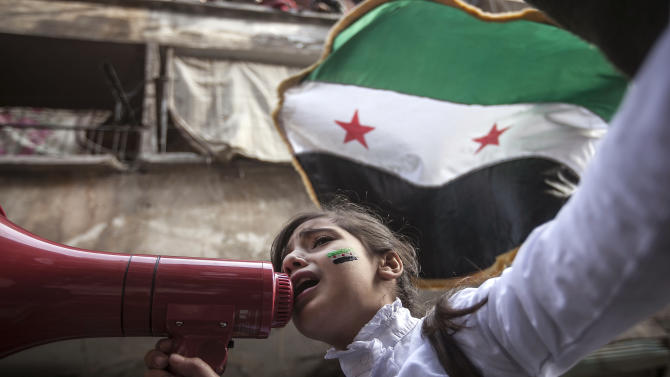 In this Friday, Nov. 30, 2012 photo, a Syrian girl chants slogans during a demonstration after Friday prayers in the Bustan Al-Qasr district of Aleppo, Syria. After months of fighting, thousands of residents have returned to the city as they attempt to return to their daily lives while heavy fighting is still taking place along the front lines in the city. Public demonstrations have unfolded after several weeks of silence as residents demand an end to the violence in Aleppo. (AP Photo/Narciso Contreras)