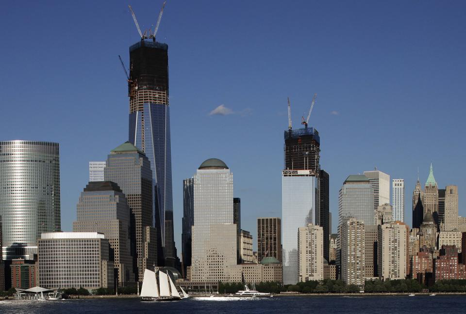 In a photo made Saturday, June 23, 2012, construction cranes perch on top of One World Trade Center, left, and Four World Trade Center in New York. Four WTC will have its topping out ceremony, in which the last steel beam is put in place, Monday, June 25.  (AP Photo/Mark Lennihan)