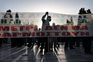 "A protester's silhouette is seen behind a banner reading: ""The measures won't apply"", as demonstrators gather in front of the parliament in Athens on April 28, 2013"