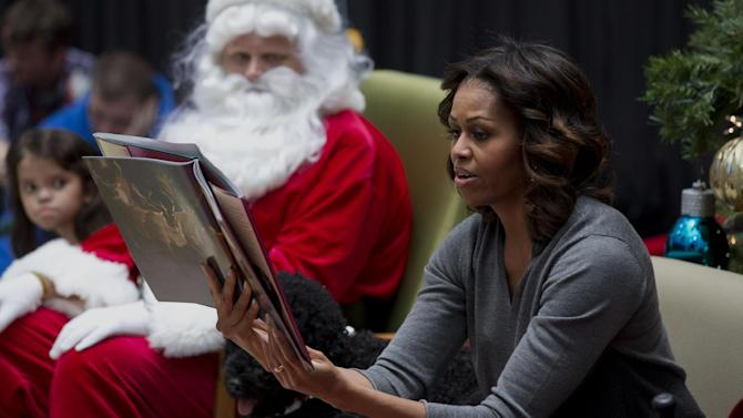 First lady Michelle Obama, accompanied by Santa Claus, reads a holiday story to children at Children's National Health System in Washington, Monday, Dec. 16, 2013. Michelle Obama read a story to children during her visit and answered questions at the Children's Hospital. (AP Photo/Jacquelyn Martin)