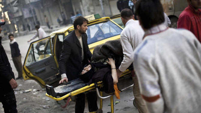 A Syrian woman injured by Syrian Army shelling lies on a gurney in front of a hospital within a Free Syrian Army controlled area in Aleppo, Syria, Friday, Dec. 14, 2012. (AP Photo/Manu Brabo)