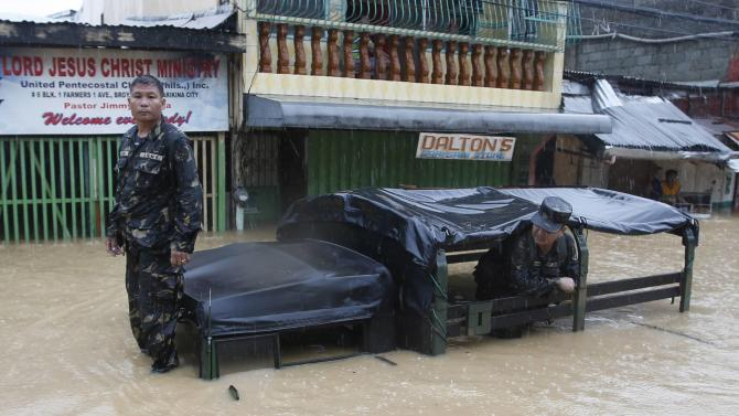 Soldiers wait for a tow truck with their stalled military rescue vehicle along a flooded road as tropical storm Fung-Wong battered the Philippine capital Manila
