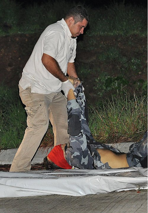 A forensic worker removes the body of slain journalist Alfredo Villatoro found on a street in Tegucigalpa, Honduras, Tuesday, May 15, 2012.  Villatoro, who was the news director for one of Honduras' m