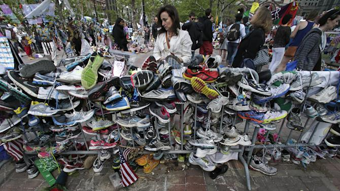Denise White, of Duxbury, Mass., center, pauses to read notes written on running shoes at the site of a memorial near the finish line of the Boston Marathon, one month after the bombing, in Boston, Wednesday, May 15, 2013. (AP Photo/Charles Krupa)