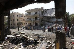 People inspect the damage at a site hit by what activists say was a car bomb in Raqqa province
