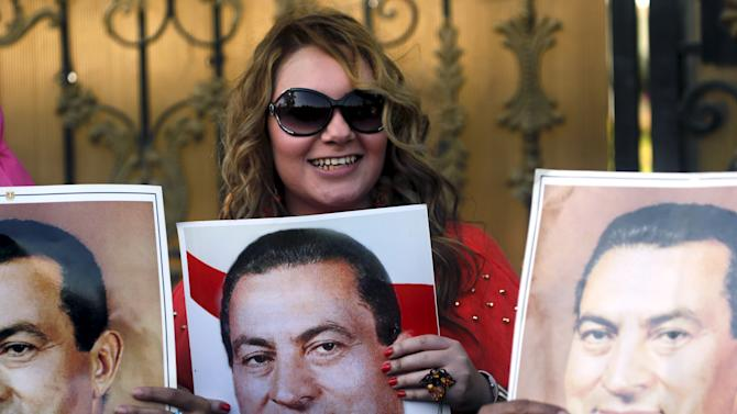 A supporter of ousted Egyptian president Hosni Mubarak cheers with a picture of him outside the area where he is hospitalized during a celebration of the 33rd anniversary of the liberation of Sinai