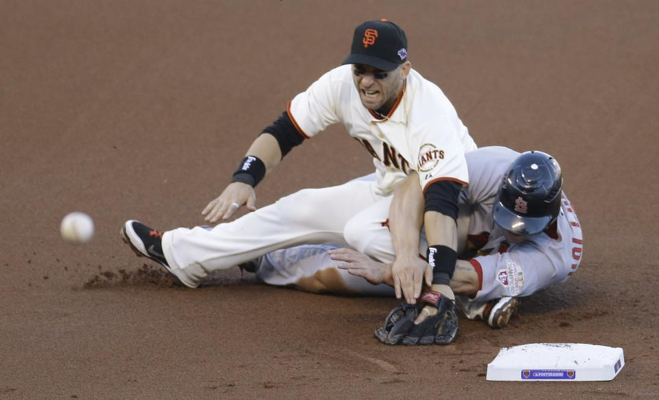 San Francisco Giants second baseman Marco Scutaro grimaces as his leg is caught under a sliding St. Louis Cardinals' Matt Holliday on a double play attempt during the first inning of Game 2 of baseball's National League championship series Monday, Oct. 15, 2012, in San Francisco. (AP Photo/Eric Risberg)