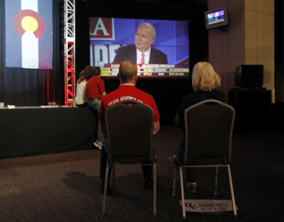 A couple sits on chairs in a near-empty room to watch Fox News commentator Karl Rove on a big-screen television during a Republican Party election night gathering in the club level of Sports Authority Field at Mile High in Denver on Tuesday, Nov. 6, 2012. (AP Photo/David Zalubowski)