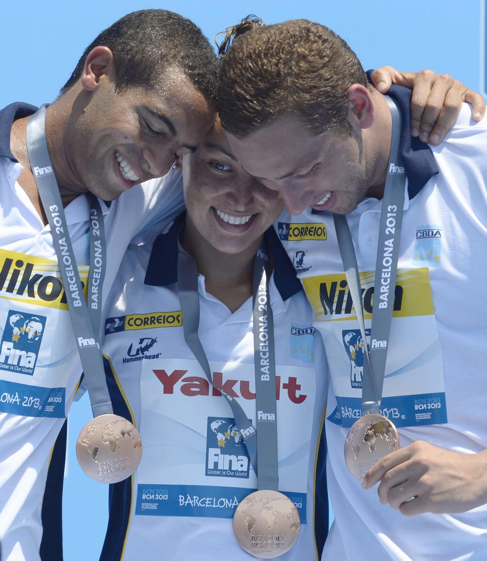 Brazilian bronze medalists from left, Allan Do Carmo, Poliana Cintra Okimoto and Samuel De Bona embrace as they celebrate following the 5km team event open water swim competition at the FINA Swimming World Championships in Barcelona, Spain, Thursday, July 25, 2013.(AP Photo/Manu Fernandez)