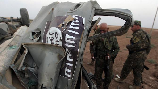 Peshmerga fighters inspect the remains of a car, bearing an image of the trademark jihadist flag, which belonged to Islamic State (IS) militants after it was targeted by an American air strike in the village of Baqufa, north of Mosul, on Aug 18,2014