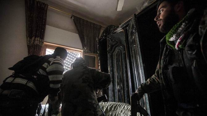 In this Tuesday, Dec. 11, 2012 photo, Free Syrian Army fighters look for government forces during heavy clashes in Aleppo, Syria. (AP Photo/Narciso Contreras)