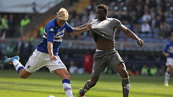 Sampdoria forward Maxi Lopez, left, pulls the jersey of Fiorentina defender Modibo Diakite during a Serie A soccer match, in Genoa, Italy, Sunday, March 30, 2014