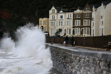 People walk along the promenade as waves crash against the seafront at Dawlish in Devon