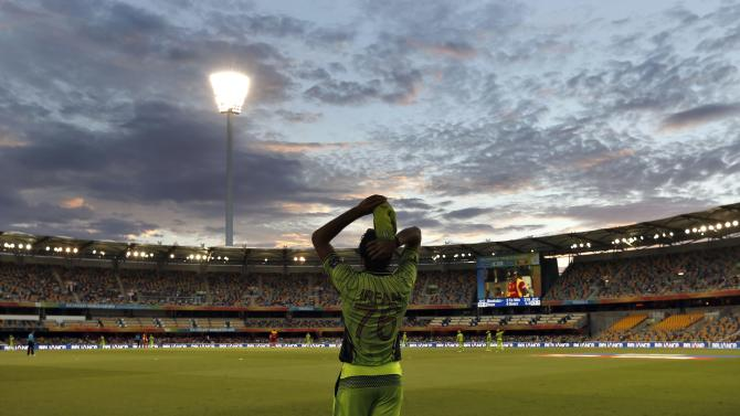 Pakistan's Mohammad Irfan adjust his hat as he fields on the boundary at sunset during the Cricket World Cup match against Zimbabwe at the Gabba in Brisbane
