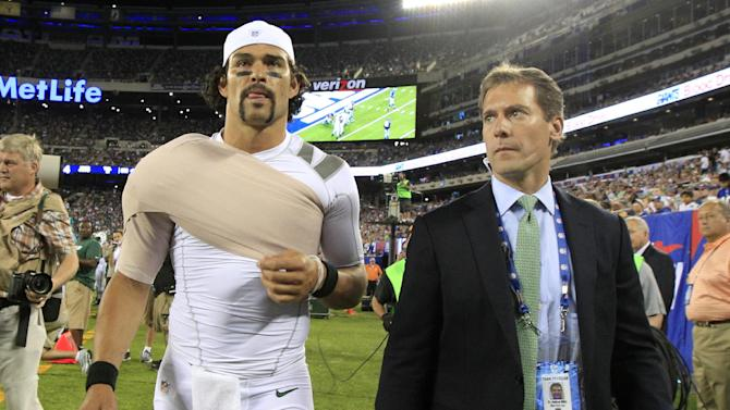 In this Aug. 24, 2013, photo, New York Jets quarterback Mark Sanchez, left, walks off the field with Dr. Andrew Willis, the team's associate orthopedist, after being injured duringa preseason NFL football game against the New York Giants in East Rutherford, N.J. On Saturday, Sept. 14, 2013, the team announced that Sanchez has been placed on injured reserve-designated for return, meaning he will not be able to play for the next eight weeks. (AP Photo/Julio Cortez)